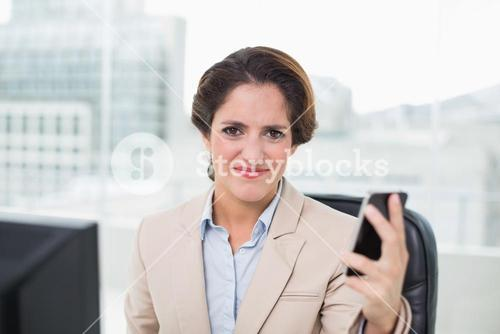 Angry businesswoman holding smartphone