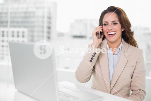 Laughing businesswoman on the phone at her desk