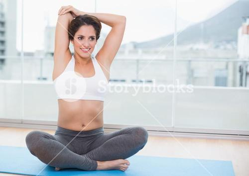 Sporty pleased brunette stretching on exercise mat