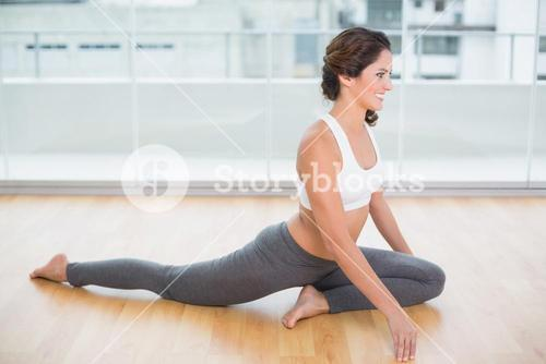 Sporty gleeful brunette stretching on the floor
