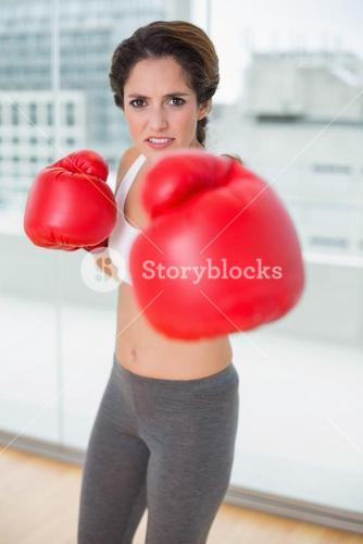Focused brunette boxing and looking at camera