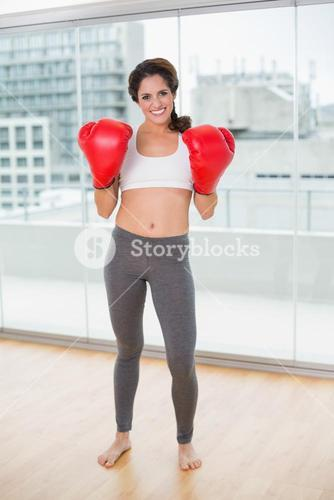 Sporty smiling brunette wearing boxing gloves