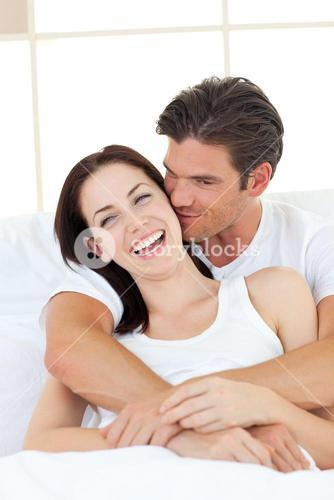 Caring man kissing his laughing wife