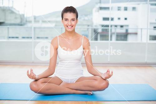 Smiling natural brown haired woman in white sportswear practicing yoga