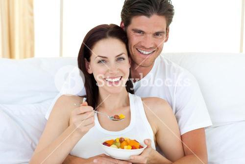 Happy couple eating fruits lying on their bed