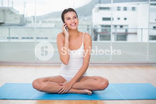 Delighted natural brown haired woman in white sportswear making a phone call