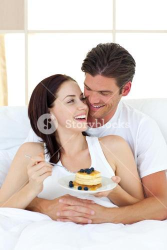 Joyful couple eating pancakes lying on their bed