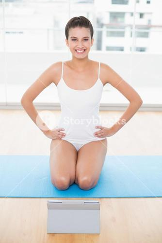 Cute natural brown haired woman in white sportswear posing with hands on the hips
