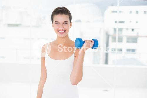 Dynamic natural brown haired woman in white sportswear lifting a dumbbell
