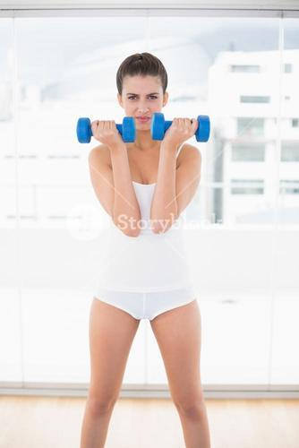 Frowning natural brown haired woman in white sportswear exercising with dumbbells