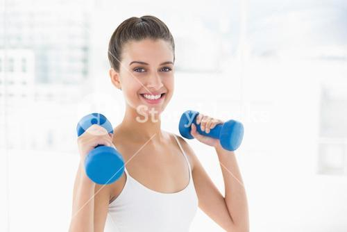 Pleased natural brown haired woman in white sportswear lifting dumbbells