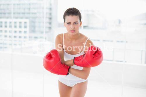 Dynamic natural brown haired woman in white sportswear wearing boxing gloves