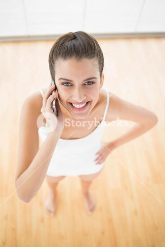Joyful natural brown haired woman in white sportswear making a phone call