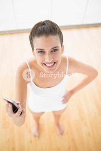 Delighted natural brown haired woman in white sportswear holding a mobile phone