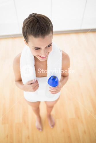 Happy natural brown haired woman in white sportswear wearing a towel and holding a sport bottle