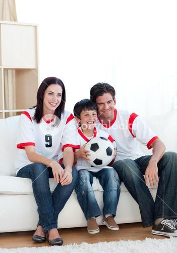 Jolly young family watching a football match