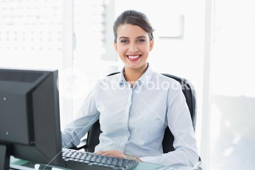 Happy classy brown haired businesswoman using a computer