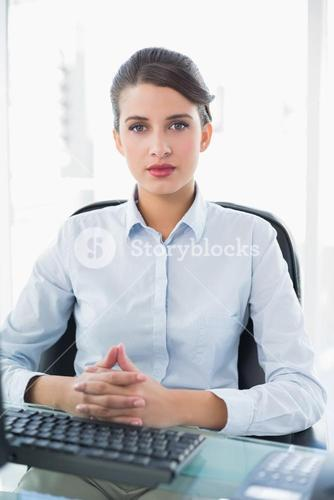 Stern classy brown haired businesswoman looking at camera
