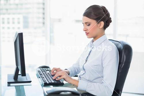 Peaceful classy brown haired businesswoman typing on a computer