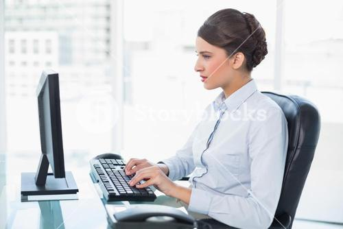 Concentrated classy brown haired businesswoman typing on a computer