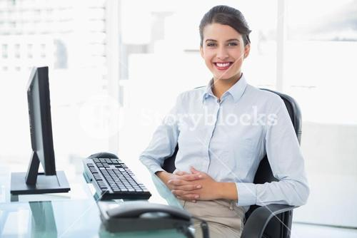 Cheerful classy brown haired businesswoman looking at camera