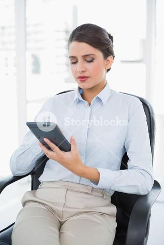 Thinking classy brown haired businesswoman using a calculator