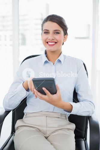 Joyful classy brown haired businesswoman using a calculator