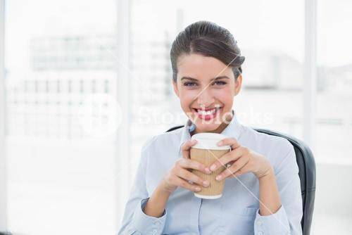 Delighted classy brown haired businesswoman enjoying coffee
