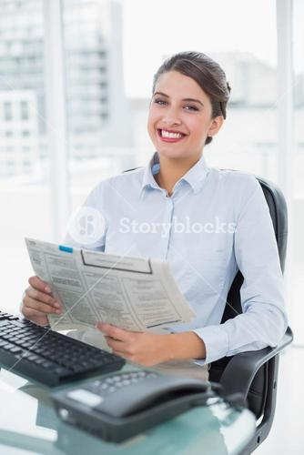 Content classy brown haired businesswoman reading a newspaper