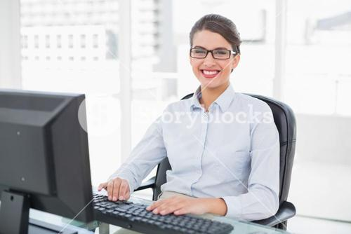 Cheerful classy brown haired businesswoman typing on a computer