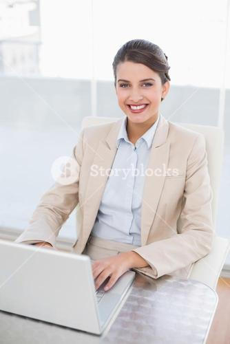 Happy smart brown haired businesswoman using a laptop