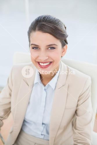 Pleased smart brown haired businesswoman looking at camera