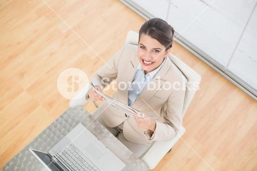 Pleased smart brown haired businesswoman reading a newspaper