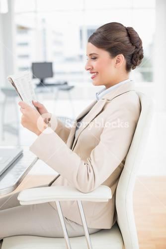 Happy smart brown haired businesswoman reading a newspaper
