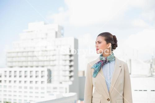Thoughtful smart brown haired businesswoman looking away