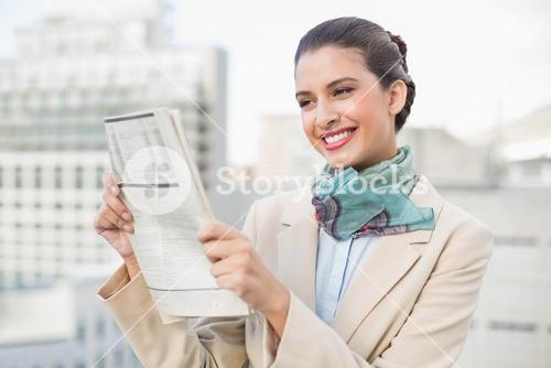 Pretty smart brown haired businesswoman reading a newspaper