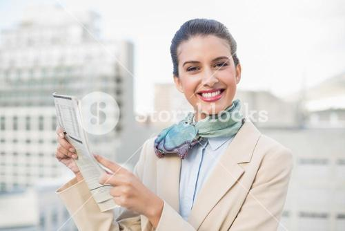 Cute smart brown haired businesswoman holding a newspaper