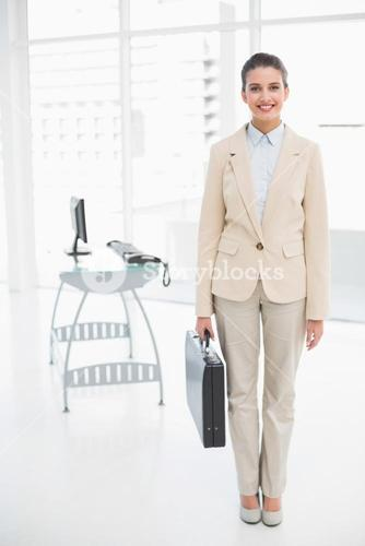 Pleased smart brown haired businesswoman carrying a briefcase