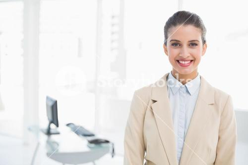 Smiling smart brown haired businesswoman looking at camera
