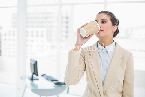 Calm smart brown haired businesswoman drinking coffee