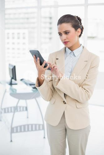 Frowning smart brown haired businesswoman using a calculator