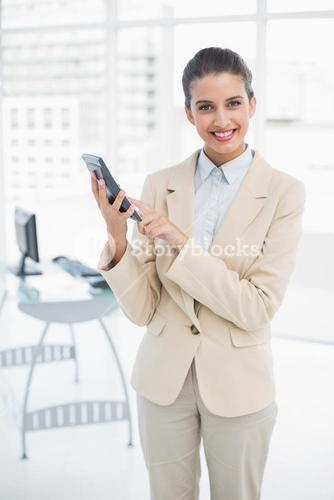 Pretty smart brown haired businesswoman using a calculator