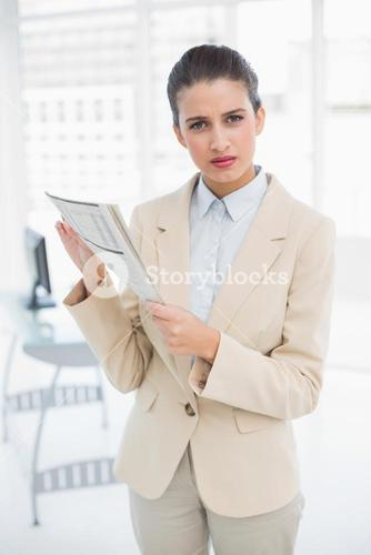 Frowning smart brown haired businesswoman holding a newspaper