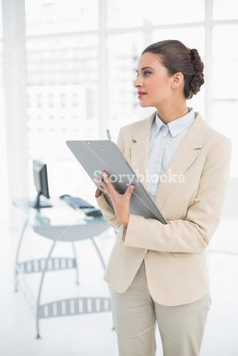 Thinking smart brown haired businesswoman checking a report