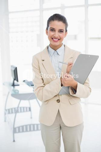 Cheerful smart brown haired businesswoman checking a report