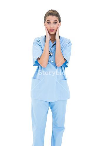 Astonished brown haired nurse in blue scrubs posing with head in hands