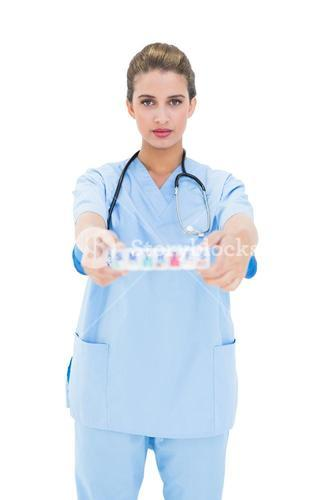 Stern brown haired nurse in blue scrubs showing a medication box