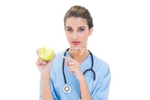 Stern brown haired nurse in blue scrubs pointing an apple with her finger