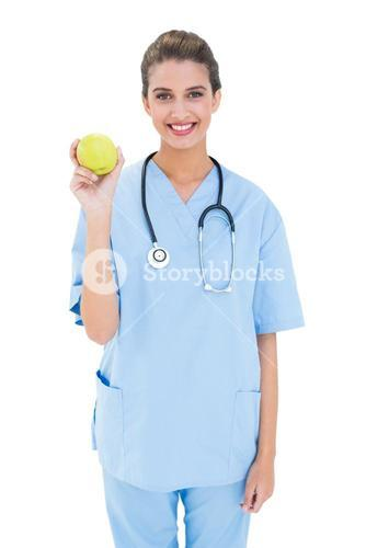 Pleased brown haired nurse in blue scrubs holding a green apple