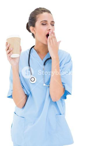 Tired brown haired nurse in blue scrubs yawning and holding a cup of coffee
